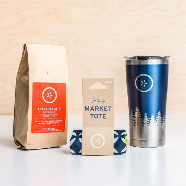Bag of Johnny's Markets Traverse City Cherry Coffee, rolled up tote bag and stainless steel travel mug with a pine tree design on a white tabletop.