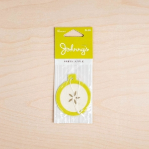 Johnny's Markets Green Apple Air Freshener in its package on a wood tabletop