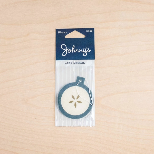 Johnny's Markets Lake Breeze Air Freshener in its package on a wood tabletop