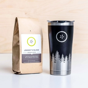 Bag of Johnny's Markets Johnny's Blend Coffee next to a stainless steel travel mug with a pine tree design.