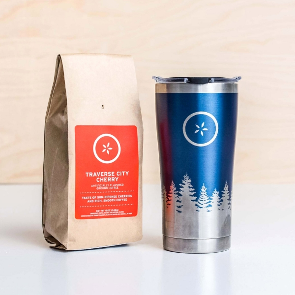 Bag of Johnny's Markets Traverse City Cherry Coffee next to a stainless steel travel mug with a pine tree design.
