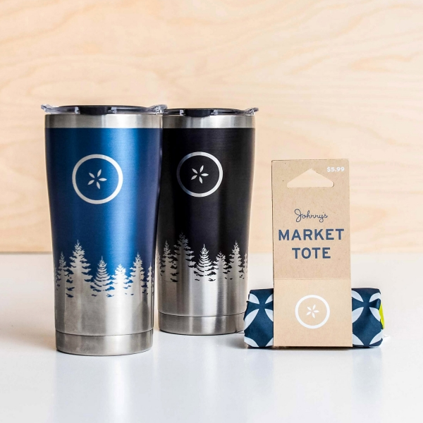 Two stainless steel travel mugs with a pine tree design — one blue and one black, next to a rolled up tote bag.