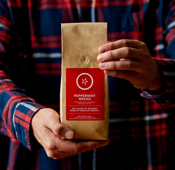 Person wearing a flannel shirt, holding a bag of Johnny's Markets Peppermint Mocha Coffee