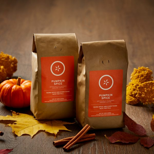 Two bags of Johnny's Pumpkin Spice Coffee on a dark wood table with cinnamon sticks and fall leaves